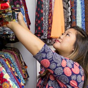 Mimi stocks her store racks
