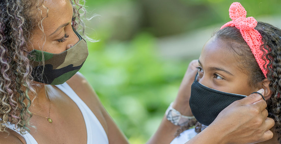 mother putting a mask on her daughter