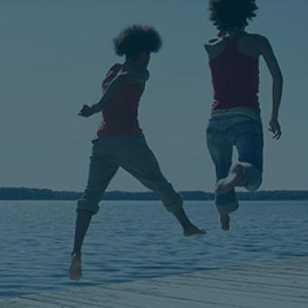 two girls jumping on a lakeside dock